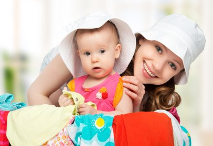 Mom and baby girl with suitcase baggage and clothes ready for traveling on vacation